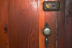 Una serratura antiquata, una maniglia di porta e un bullone morto su una porta di legno Immagine Stock