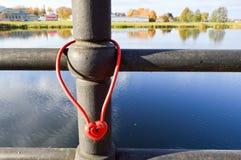 Una serratura rossa del granaio sotto forma di un cuore appende sull'inferriata di un ponte La tradizione di nozze da appendere f fotografia stock libera da diritti