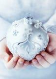 Una sfera di natale dell'argento della holding del bambino Fotografia Stock