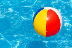 Una sfera di spiaggia variopinta che galleggia in una piscina Fotografie Stock