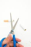 Una sigaretta di taglio della mano Immagine Stock