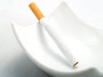 Una sigaretta in un portacenere bianco pulito Fotografia Stock Libera da Diritti