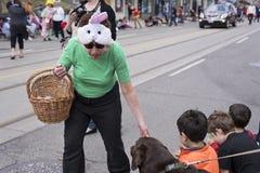 Una signora anziana che porta il cappello sveglio del coniglietto di pasqua distribuisce i regali alla c Immagini Stock