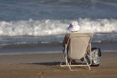 Una signora anziana che si siede in una presidenza sulla spiaggia Immagini Stock Libere da Diritti