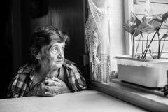 Una signora anziana si siede tristemente vicino alla finestra della sua vecchia casa Immagini Stock Libere da Diritti