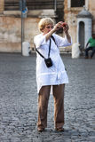Una signora anziana sta facendo un'immagine della foto Fotografia Stock Libera da Diritti