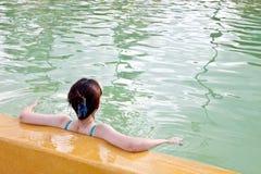 Una signora asiatica che si distende nella piscina immagini stock
