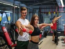 Una signora che fa gli esercizi con le teste di legno rosse su un fondo della palestra Un istruttore personale che aiuta un clien immagine stock