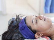 Una signora che si prepara per la procedura cosmetica di abbellimento facciale della stazione termale con la banda capa protettiv immagini stock libere da diritti