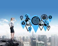Una signora di affari sta progettando gli obiettivi di affari stando nella roccia Fotografia Stock