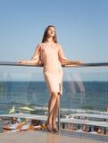 Una signora elegante su un fondo del cielo blu Una ragazza pacifica in un vestito rosa Una giovane donna romantica su una vacanza Fotografia Stock