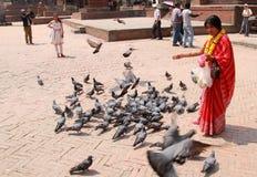 Una signora nepalese in panno tradizionale e ghirlanda gialla che alimentano i piccioni Immagini Stock