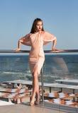 Una signora sbalorditiva che posa su un fondo luminoso della spiaggia Una ragazza ideale in un vestito dalla rosa su un terrazzo  Fotografie Stock Libere da Diritti
