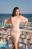 Una signora sbalorditiva che posa su un fondo luminoso della spiaggia Una ragazza ideale in un vestito dalla rosa su un terrazzo  Fotografia Stock