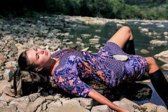 Una signora sta esponendo al sole sulla spiaggia di un fiume della montagna Immagine Stock Libera da Diritti