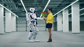 Una signora sta ottenendo i fiori da un cyborg alto archivi video