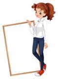 Una signora in un abbigliamento convenzionale che sta davanti all'insegna Immagine Stock