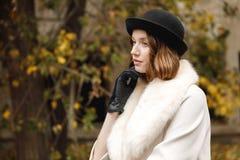 Una signora in un cappello, in guanti ed in un cappotto leggero sta guardando fuori, tenendo la sua mano dal fronte retro all'ape fotografie stock
