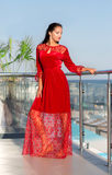 Una signora in un vestito rosso che posa su un fondo soleggiato della località di soggiorno Una giovane donna elegante su un balc immagini stock libere da diritti