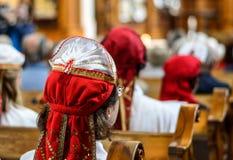 Una signora in vestiti tradizionali che si siedono in una chiesa Fotografia Stock