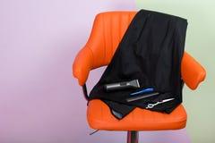 una silla anaranjada en la cual un sistema de artículos es una herramienta para cortar el pelo y la barba, una variedad de tijera fotografía de archivo