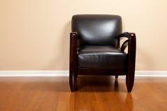 Una silla de cuero negra vacía en casa Imágenes de archivo libres de regalías