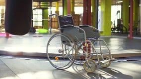 Una silla de ruedas está en el gimnasio El concepto de lesión de los deportes MES lento almacen de metraje de vídeo