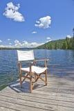 Una silla en el muelle de un lago hermoso Imagen de archivo libre de regalías