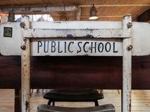 Una silla vieja agradable del estudio delante de un escritorio con la escuela pública de las palabras impresa en la parte posteri imagen de archivo libre de regalías