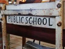 Una silla vieja agradable del estudio delante de un escritorio con la escuela p?blica de las palabras impresa en la parte posteri fotos de archivo libres de regalías