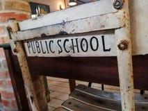 Una silla vieja agradable del estudio delante de un escritorio con la escuela p?blica de las palabras impresa en la parte posteri imagen de archivo libre de regalías