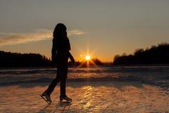 Una silueta de una mujer con los patines de hielo en la puesta del sol Imagen de archivo