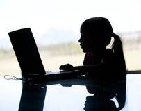 Una silueta de un niño joven que mira en el ordenador.  Depi de mayo Fotos de archivo