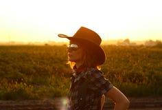 Una silueta de una vaquera con una puesta del sol hermosa en el fondo Fotos de archivo