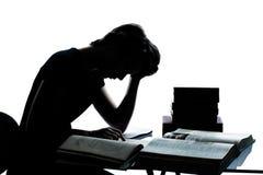Una silueta del adolescente que estudia el ti de los libros de lectura Fotografía de archivo