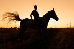 Una silueta del jinete a caballo en la puesta del sol Imagen de archivo libre de regalías