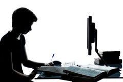 Una silueta joven de la muchacha del muchacho del adolescente que estudia con el ordenador c Fotografía de archivo