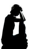 Una silueta joven de la tristeza del muchacho o de la muchacha del adolescente que pone mala cara Foto de archivo