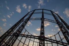 Una silueta llamativa de un cilindro vacío del almacenamiento de gasolina contra el cielo de la oscuridad en Londres del este foto de archivo