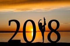 Una siluetta da 2018 nuovi anni del dancing della ragazza al tramonto dorato Fotografie Stock