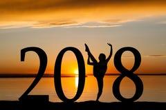 Una siluetta da 2018 nuovi anni del dancing della ragazza al tramonto dorato Fotografia Stock
