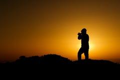 Una siluetta del cineoperatore con indicatore luminoso dorato Fotografia Stock