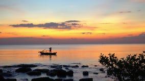 Una siluetta della piccola barca con il pescatore al tramonto Barca sull'orizzonte di tramonto del mare aperto Bello declino gial stock footage