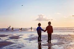 Una siluetta di due bambini, surfisti di sorveglianza sulla spiaggia Fotografie Stock Libere da Diritti