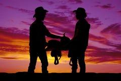 Una siluetta di due cowboy che tengono una sella nel tramonto Fotografie Stock