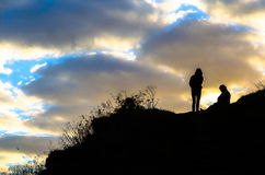 Una siluetta di due donne su una collina al tramonto Immagine Stock Libera da Diritti
