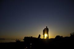 Una siluetta di due genti che si levano in piedi su una banca Fotografie Stock Libere da Diritti