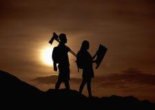 Una siluetta di due macchine fotografiche d'escursione e di trasporto della gente e di una mappa in natura al tramonto Fotografie Stock