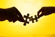 Una siluetta di due mani collega insieme il puzzle Fotografia Stock Libera da Diritti