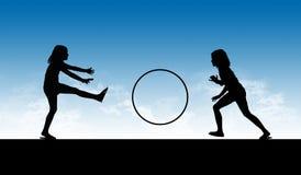 Una siluetta di due ragazze che giocano con un cerchio Fotografia Stock Libera da Diritti